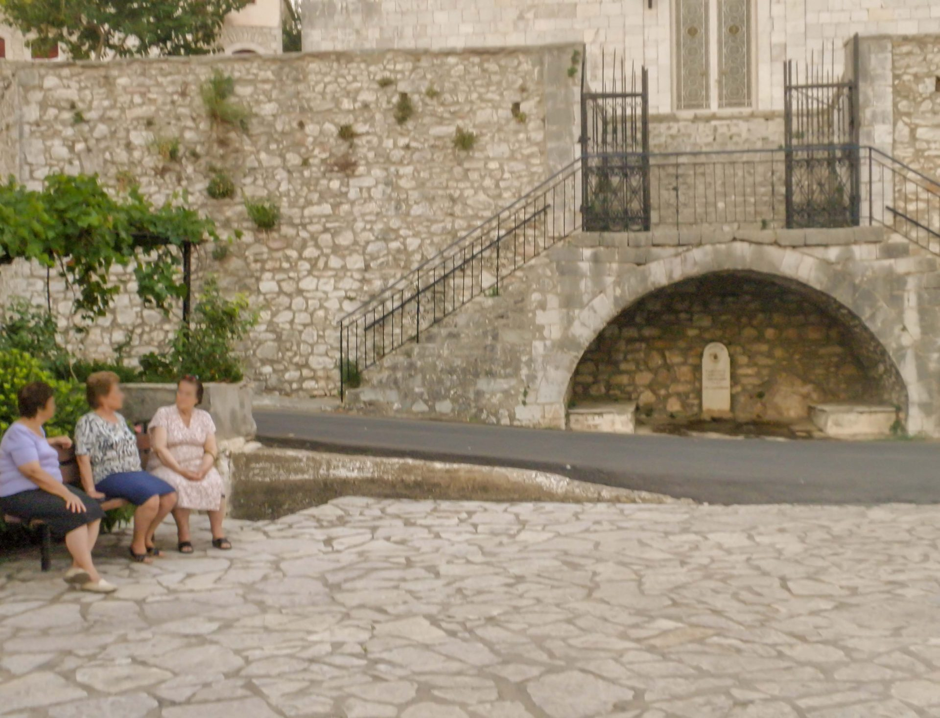 Greek church of Karytaina with local women chatting on a bench.